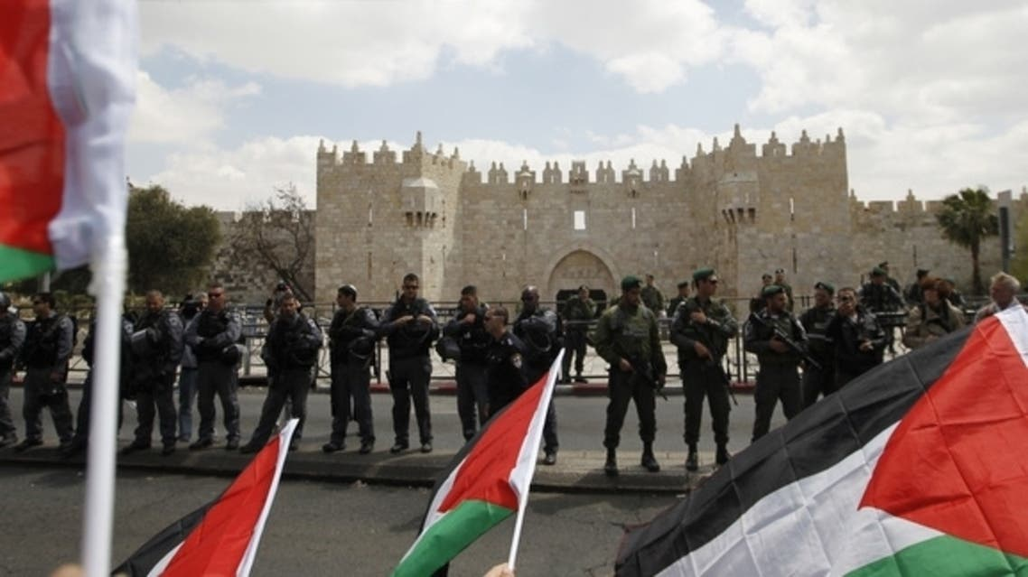 Protesters hold Palestinian flags opposite Israeli security officers standing guard before Friday prayers on Land Day outside Damascus Gate in Jerusalem's Old City, March 30, 2012. (Reuters)