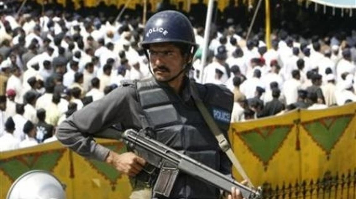 A policeman stands guard during a funeral for policemen who were killed in an attack at a police training center in Lahore. (Reuters)