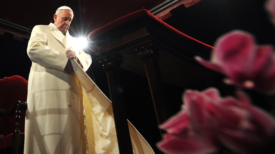 Pope Francis puts his coat on during the celebration of the Good Friday at the Colosseum in Rome. (AFP)