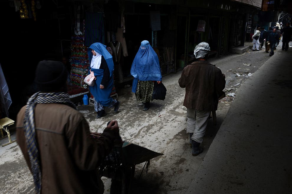Afghan women and laborers with wheelbarrows walk down a lane in Kabul. Much of Afghanistan's money is in an undocumented black economy. (AFP)