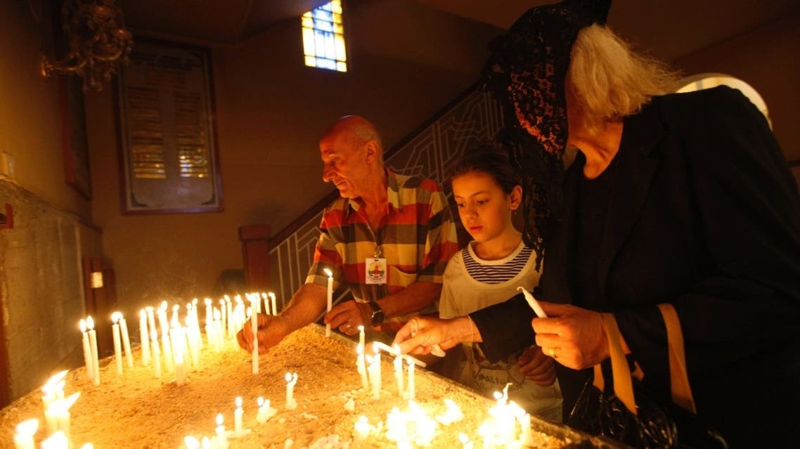Iraqi Christians light candles during an Easter Mass at a Church in Baghdad. (Reuters)