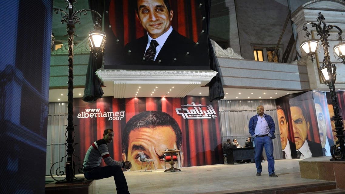Egyptians walking past posters of TV satirist Bassem Youssef outside a theatre in Cairo. (AFP)