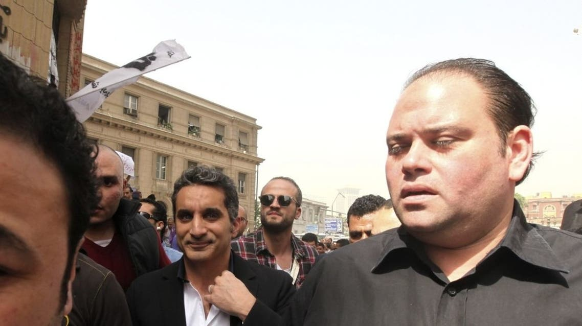 Bodyguards surround Bassem Youssef (C), the country's best-known satirist, as he arrives at the high court to appear at the prosecutor's office in Cairo. (Reuters)