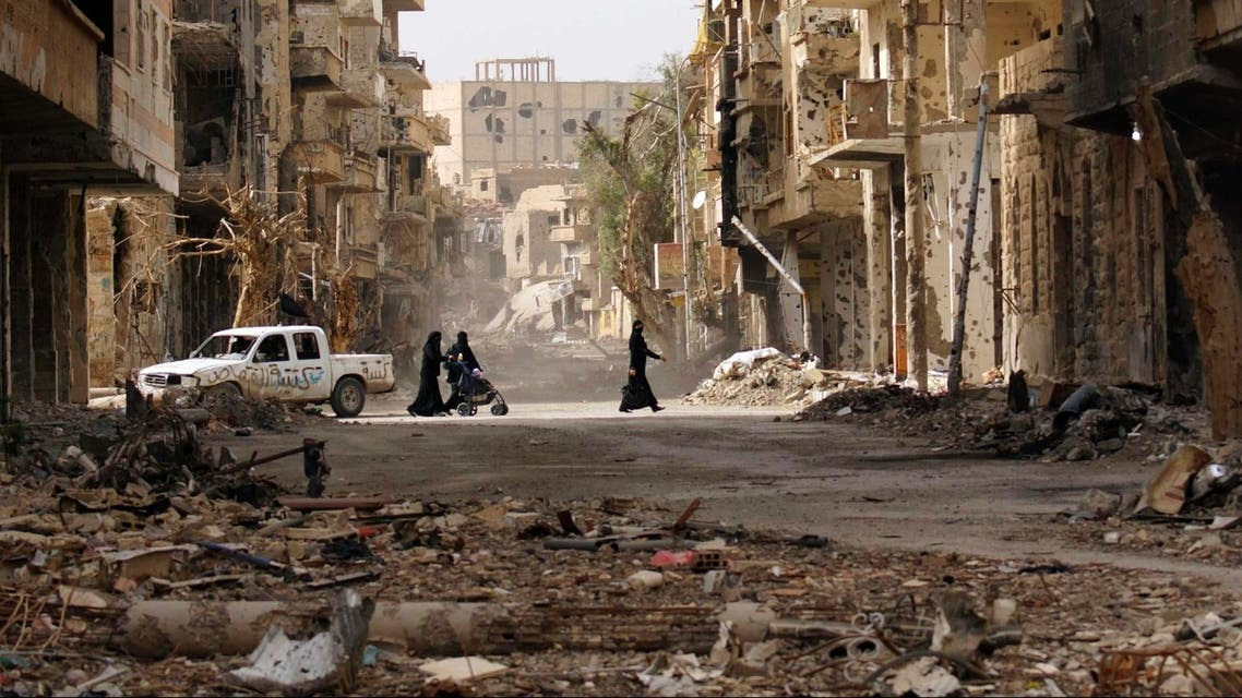 Women walk along a damaged street filled with debris in Deir al-Zor, Syria. Earlier this year, NGO Save the Children warned of increased child abandonment in a special report on the plight of Syria's youth. (Reuters)