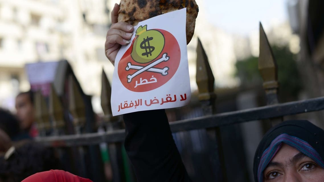 """An Egyptian protester holds bread along with a flyer reading in Arabic """"danger, no to loans that lead to poverty"""". (AFP)"""