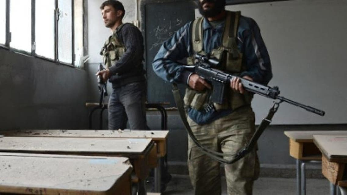 Syrian rebels take position inside a building to observe the movement of regime forces. (AFP)