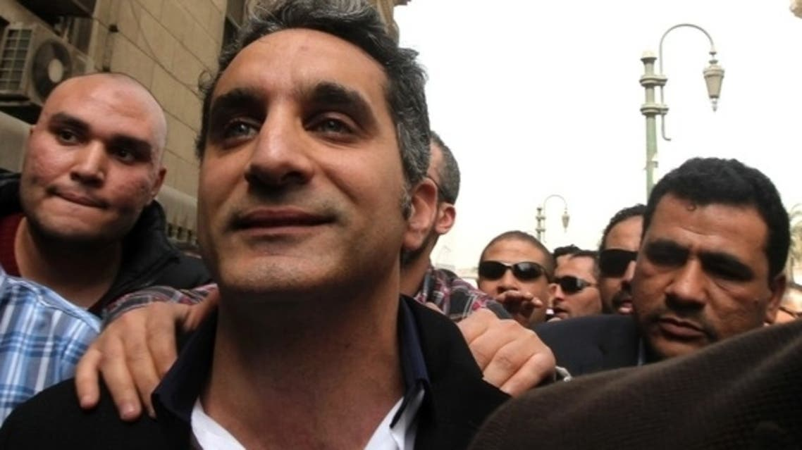 Bassem Youssef, the country's best-known satirist, gestures to journalists and activists as he arrives at the high court to appear at the prosecutor's office in Cairo March 31, 2013. (Reuters)