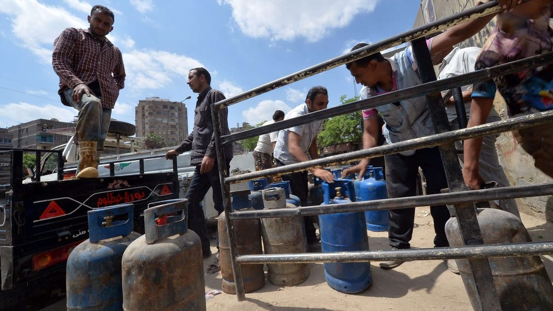 An Egyptian man loads gas cylinders onto a truck. Egypt hiked the price of subsidized cooking gas by 60 percent, triggering market chaos. (AFP)