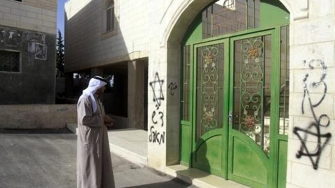 A Palestinian looks at Hebrew grafittis sprayed on the walls of a mosque on April 7, 2013 in the West Bank village of Tuqua