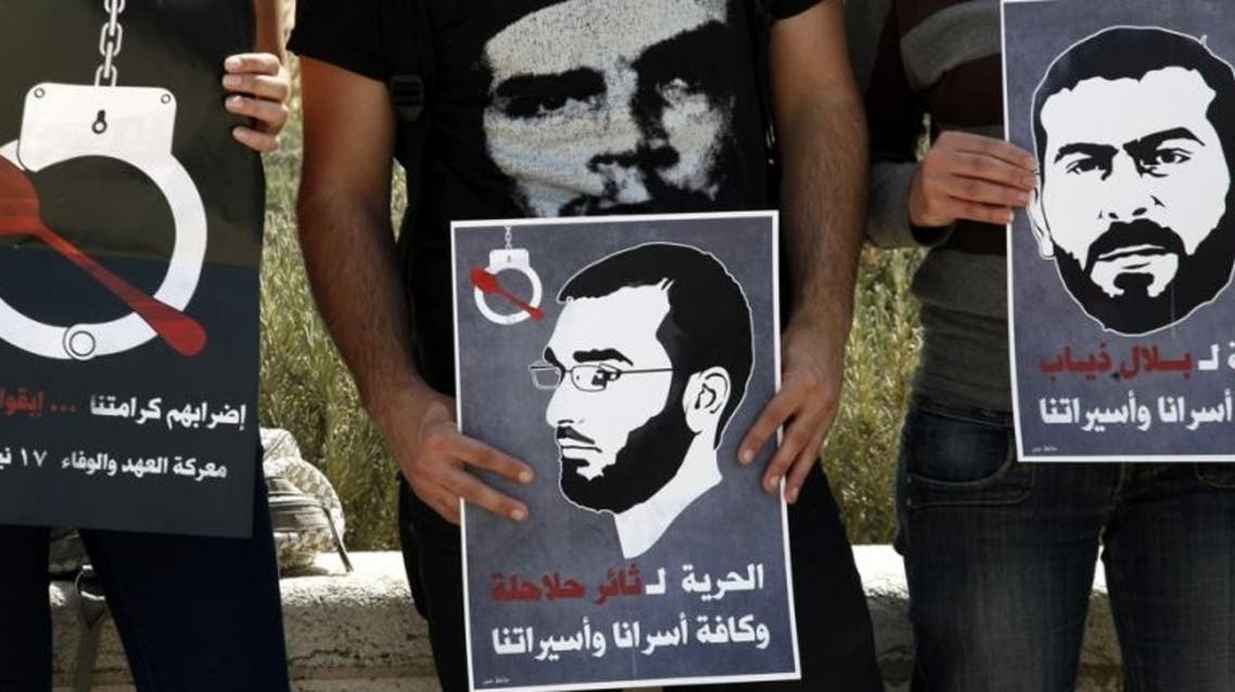 Palestinian protesters hold posters depicting Palestinian hunger strikers Thaer Halahla and Bilal Thiab who are in administrative detention during a protest outside Israel's Supreme Court in Jerusalem on 3 May 2012. (Photo: AFP
