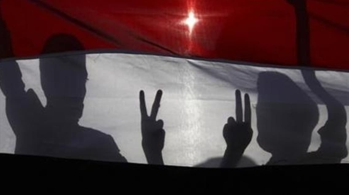 Boys posing with the victory sign are silhouetted against Yemen's national flag at a rally in Sanaa September 18, 2012, commemorating people killed during last year's unrest against former Yemeni president Ali Abdullah Saleh.