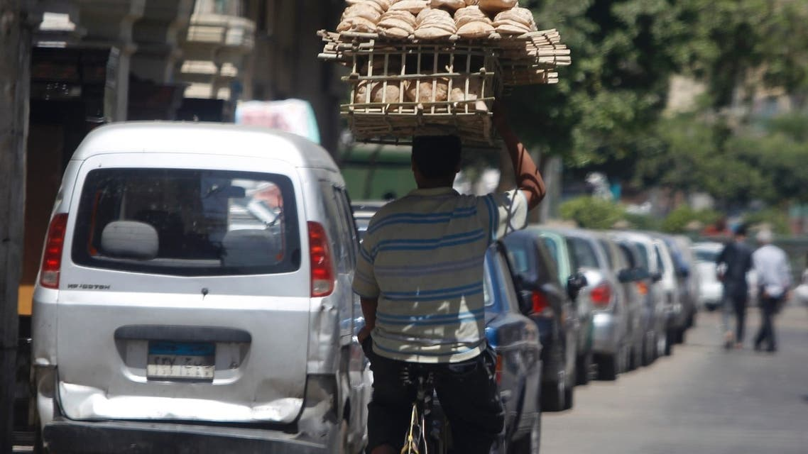 A man carries bread to be sold to customers in Cairo. Ministers in Egypt – which is in talks over a $4.8bn IMF loan - fear possible fuel and food shortages. (Reuters)