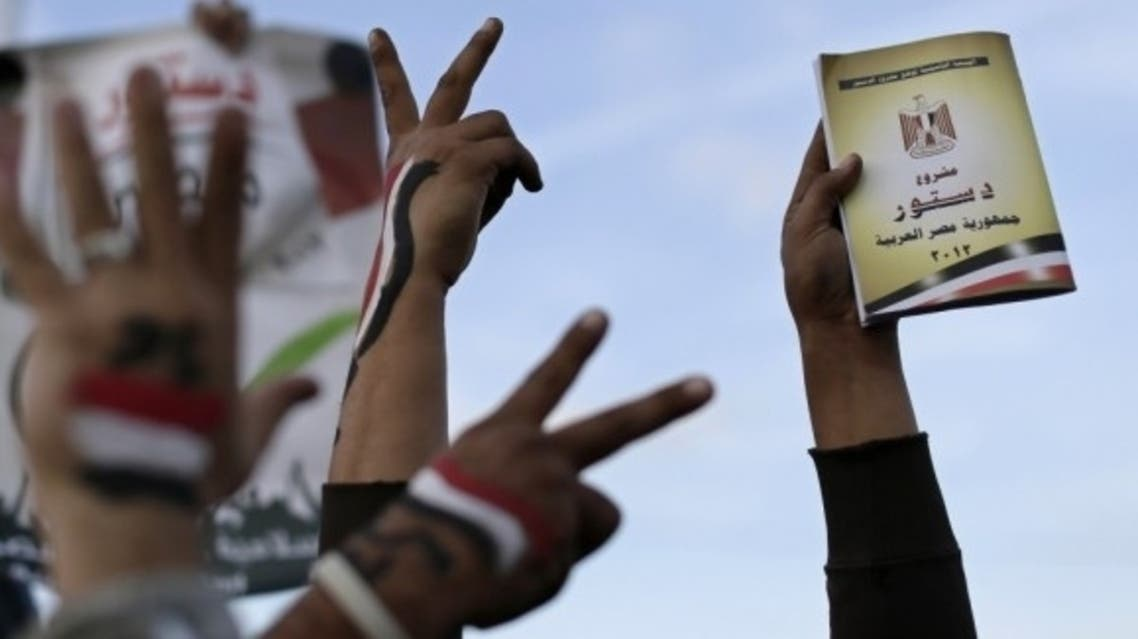 Supporters of President Mohammed Morsi holdsa copy of Egypt's draft constitution during a demonstration in Cairo on Dec. 11, 2012. (Courtesy: AP)