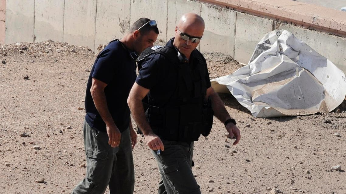 Israeli police explosives experts walk near a rocket which was fired into the Red Sea resort city of Eilat April 17, 2013. (Reuters)