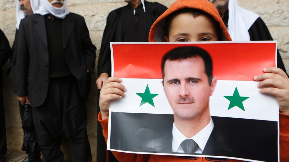 A boy from the Druze community holds a Syrian flag with the image of Syria's President Bashar al-Assad during a rally marking Syria's Independence Day. (Reuters)