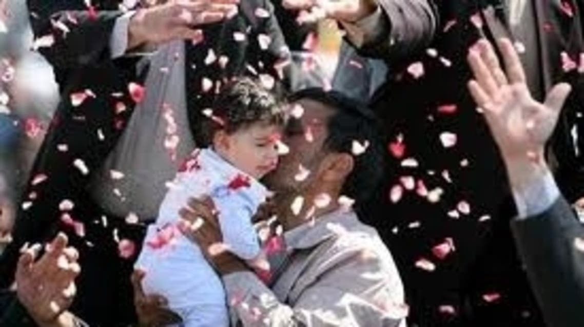 Iran's President Mahmoud Ahmadinejad hugs a child and is showered with flower petals during his visit to Semnan, Iran, in 2009. AP
