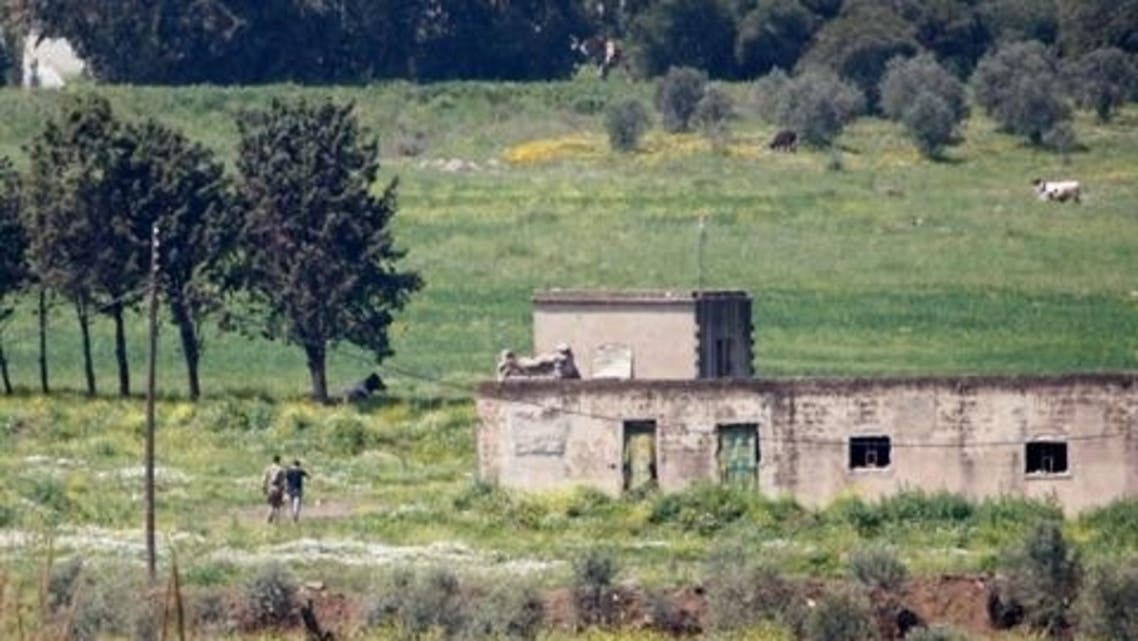 Syrian soldiers walk in a field in the Syrian village of Al Arida Al Gharbia as seen from the northern Lebanese village of Wadi Khaled near the Lebanese-Syrian border