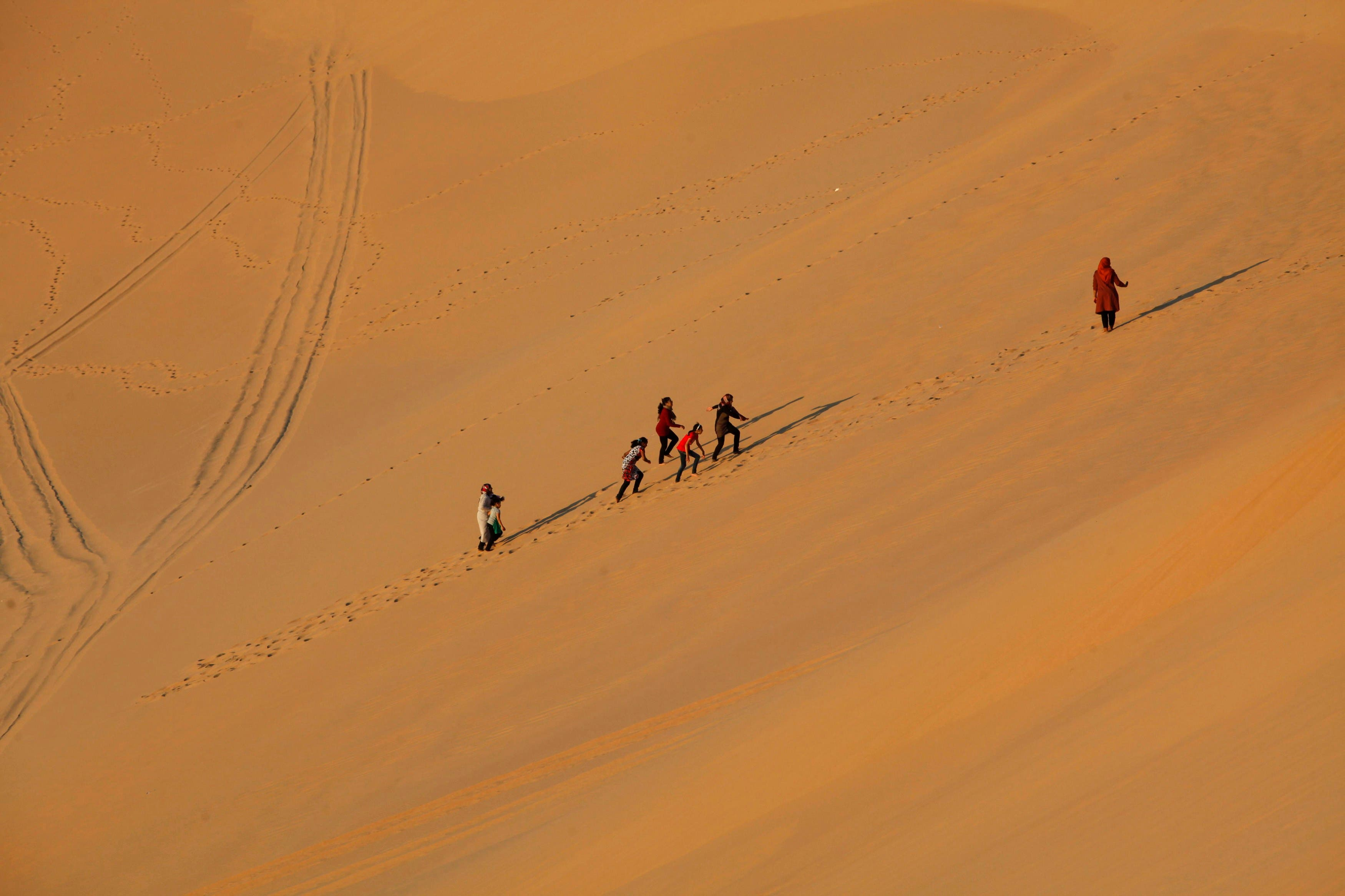 Residents walk on sand dunes in the Libyan desert oasis town of Ghadames (Reuters)