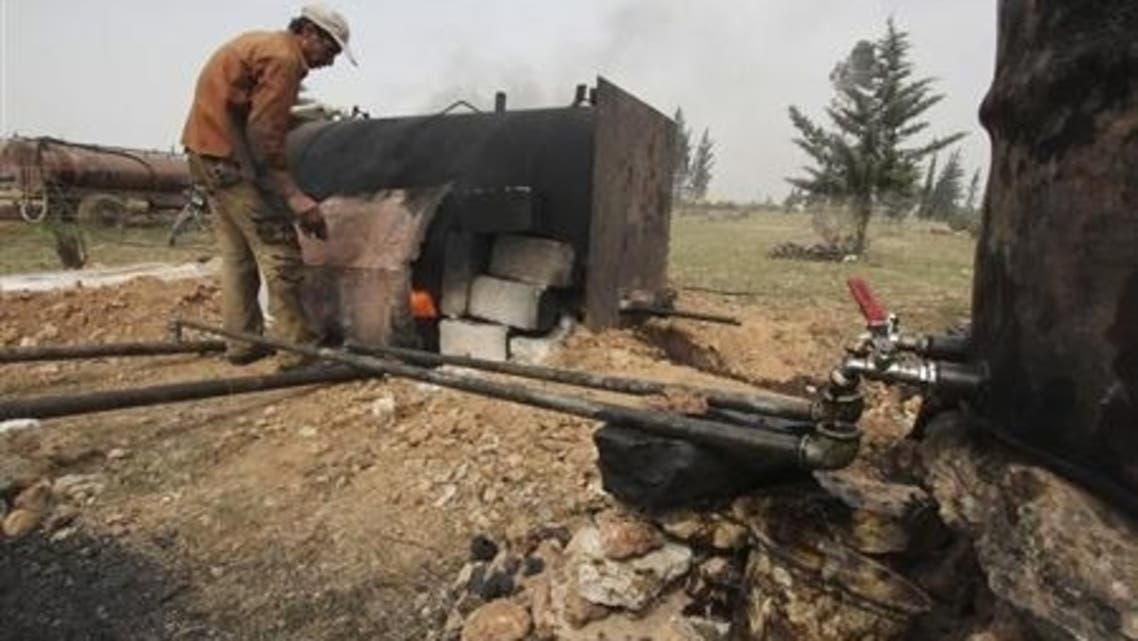 A man works at a makeshift oil refinery site in Aleppo's countryside April 2, 2013.