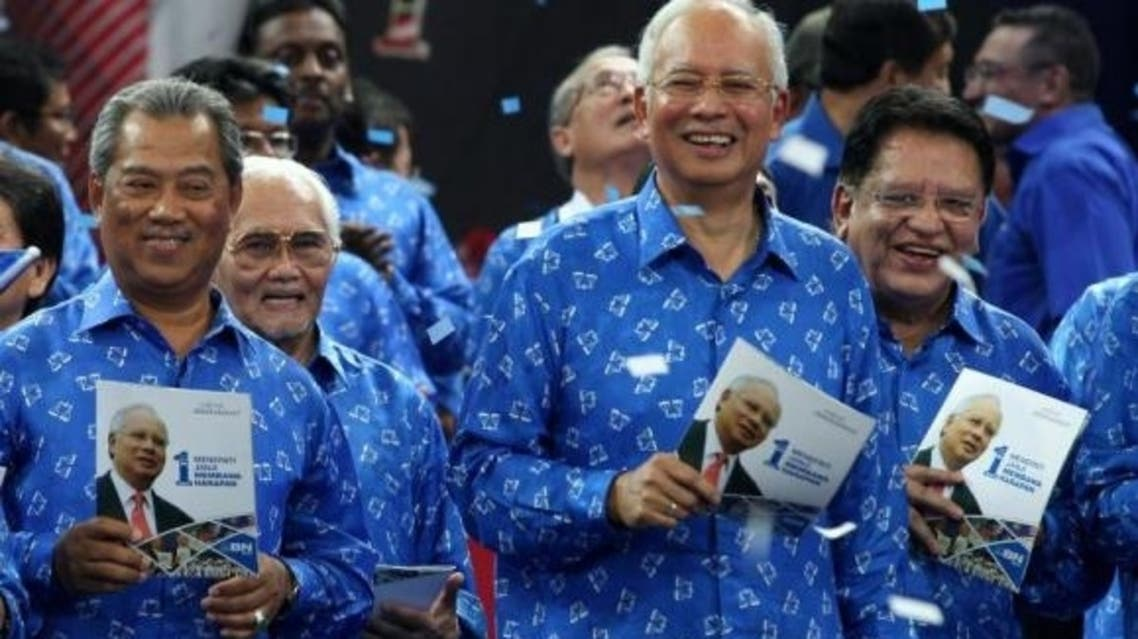Malaysian PM Najib Razak (2R) smiles as he holds a copy of his coalition's election manifesto with other members party ahead of upcoming polls in Bukit Jalil, Kuala Lumpur, in this April 6, 2013 file photo. (AFP)