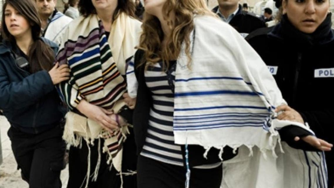 Israeli police arrest American Rabbi Susan Silverman (L), sister of comedian Sarah Silverman, and her teenage daughter Hallel Abramowitz (C), after performing Rosh Hodesh prayers at the Western Wall ina Jerusalem, on February 11, 2013 (AFP)