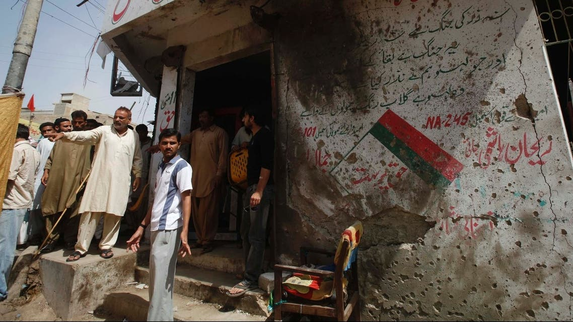 Men stand outside the campaign office of the Muttahida Qaumi Movement (MQM) political party, after Thursday's bomb blast in Karachi April 26, 2013. REUTERS