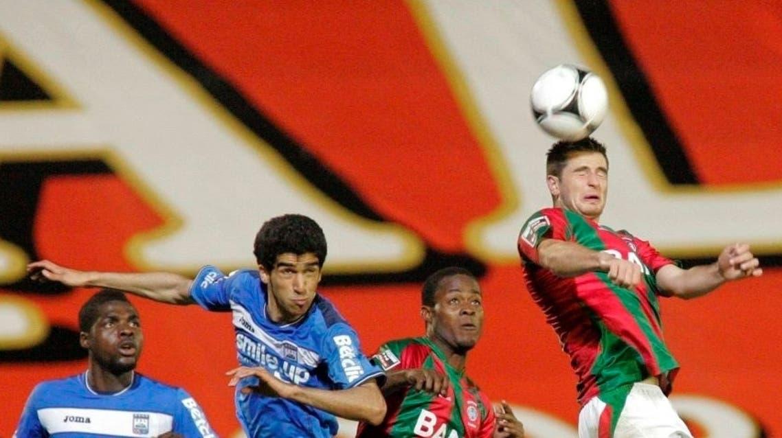 عبدالله الحافظ بقميص فريقه البرتغالي (الأزرق) يسدد الكرة برأسه
