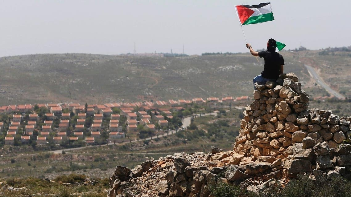 A protester waves a Palestinian flag in front of the Jewish settlement of Ofra during clashes near the West Bank village of Deir Jarir near Ramallah April 26, 2013. (Reuters)