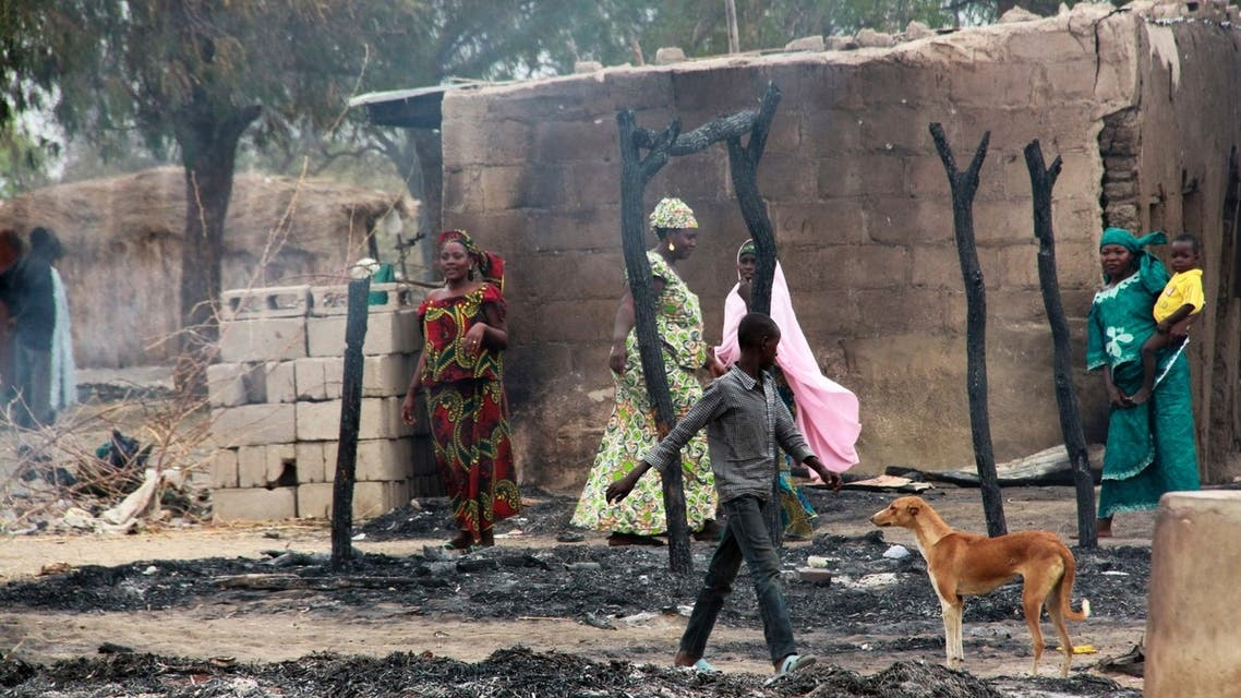 People stand near burnt structures in the aftermath of what Nigerian authorities said was heavy fighting between security forces and Islamist militants in Baga