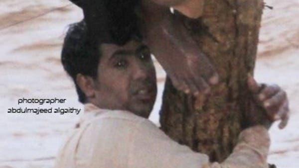 سعودي يتمسك بشجرة خوفاً من أن تسحبه السيول