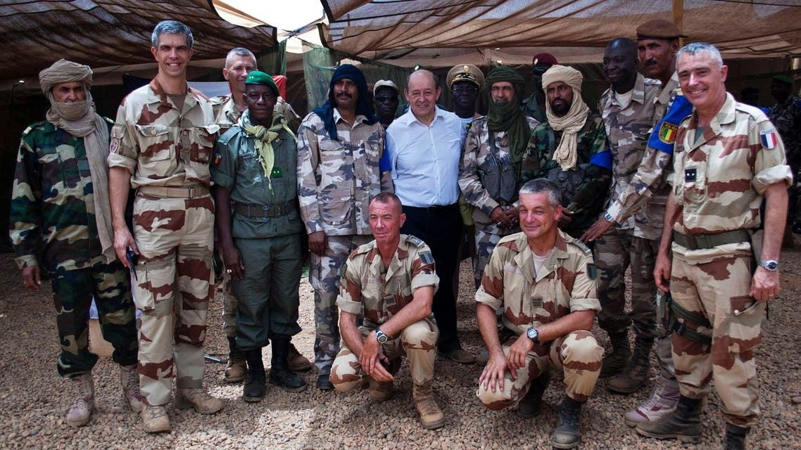 French Defence Minister Jean-Yves Le Drian (C) poses for a picture with French and Malian army officers at the French military base at the airport in Gao, April 26, 2013. (Reuters)