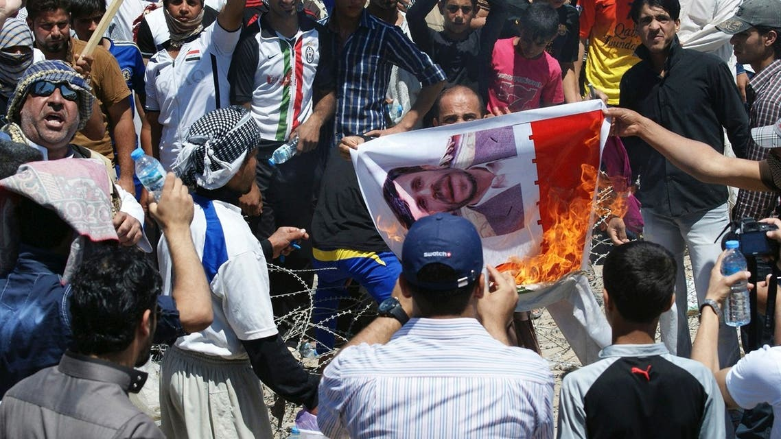 Iraqi Sunni Muslims burn a poster of Iranian President Mahmoud Ahmadinejad during an anti-government demonstration in Falluja, 50 km (31 miles) west of Baghdad April 26, 2013. (REUTERS)