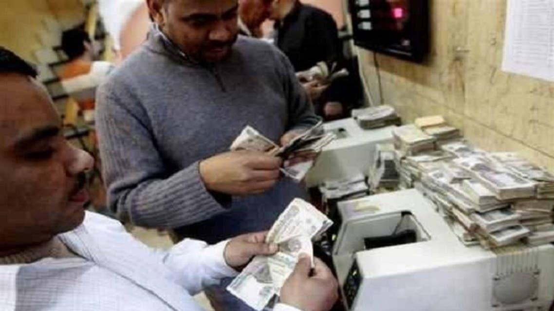 Men count bank notes at a foreign exchange office in the center of Cairo. Qatar wants 5 percent interest on $3 billion in bonds it has offered to buy from Egypt, an Egyptian official said. (Reuters)