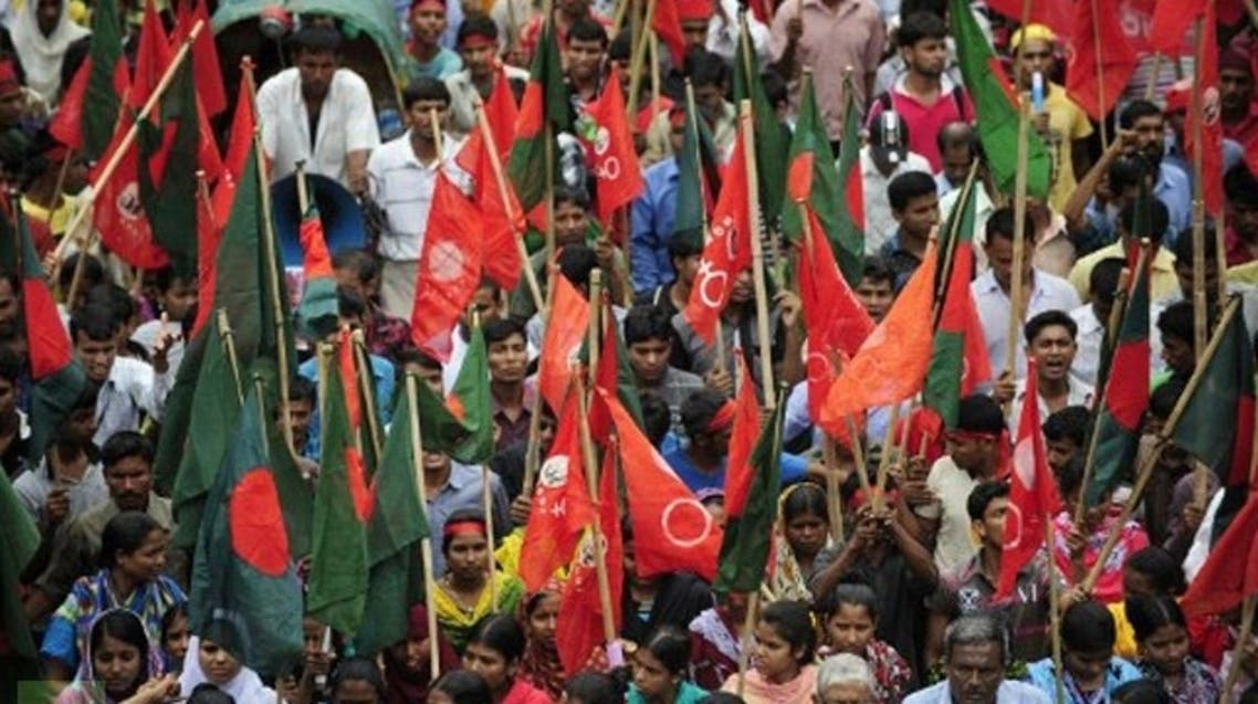 Bangladeshi activists shout slogans and wave flags during a procession to mark May Day in Dhaka. (AFP)