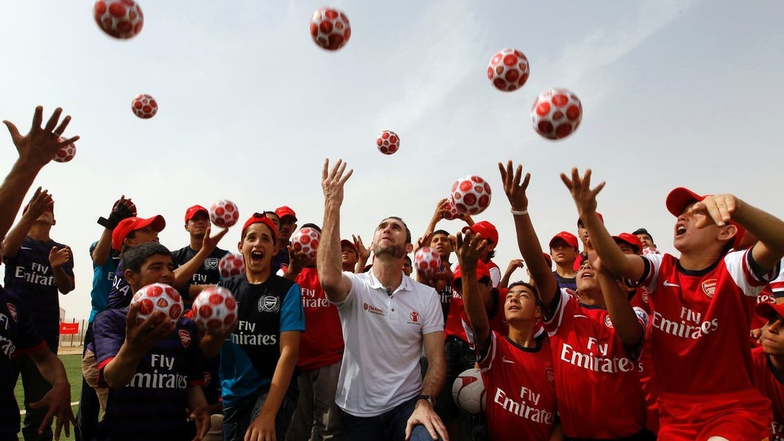 Martin Keown (C), a former British soccer player for Arsenal, and Syrian refugee children throw balls into the air during the official opening of Save the Children's new soccer field at the Al Zaatri refugee camp in the Jordanian city of Mafraq, near the border with Syria, May 2, 2013. Keown's visit is part of soccer club Arsenal's global partnership with humanitarian group Save the Children's education projects. (Reuters)