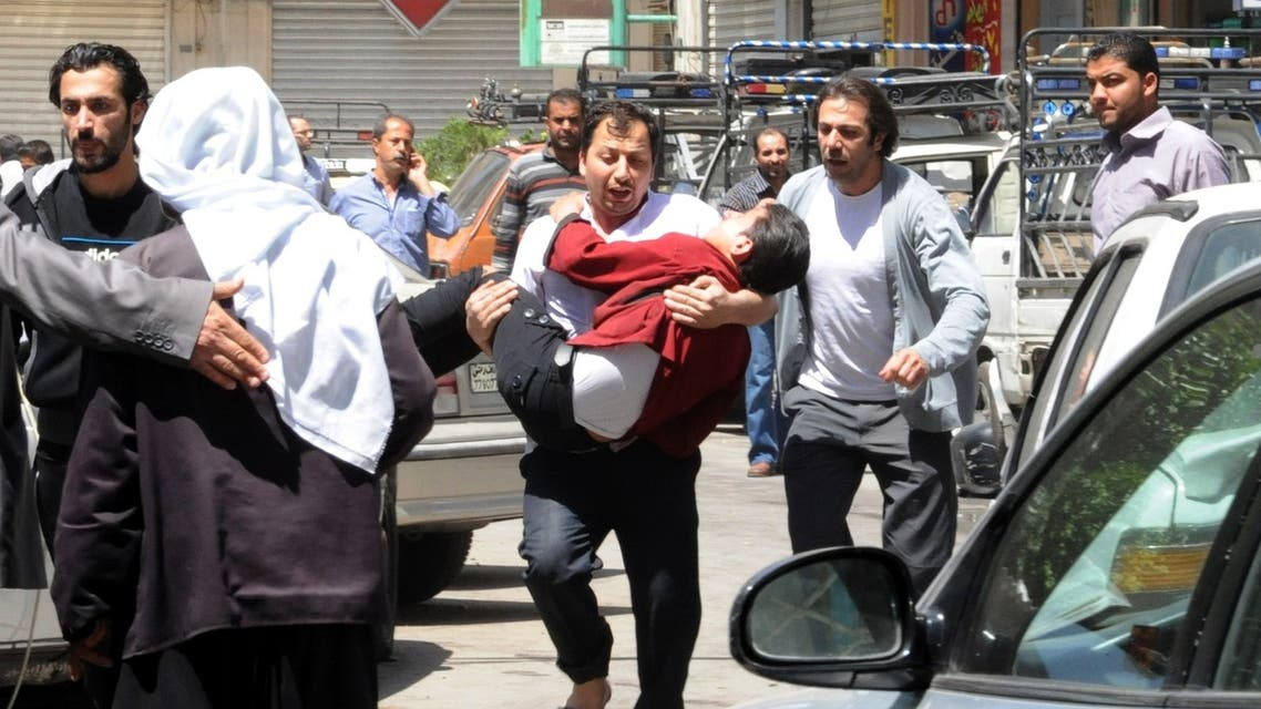 DAM10 - Damascus, -, SYRIA : TOPSHOTS A handout picture released by the Syrian Arab News Agency (SANA) on April 30, 2013, shows a Syrian man carrying an injured person following a blast in the Marjeh district of Damascus. (AFP)