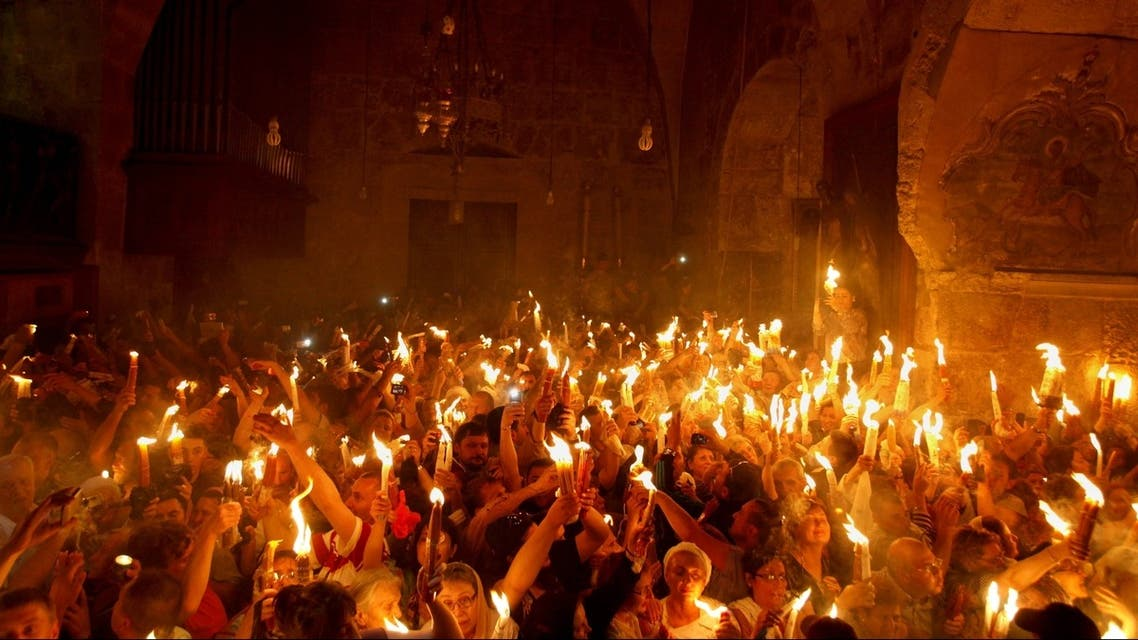 Christian Orthodox worshippers hold up candles lit from the 'Holy Fire' as thousands gather in the Church of the Holy Sepulchre in Jerusalem's old city on May 4, 2013 AFP