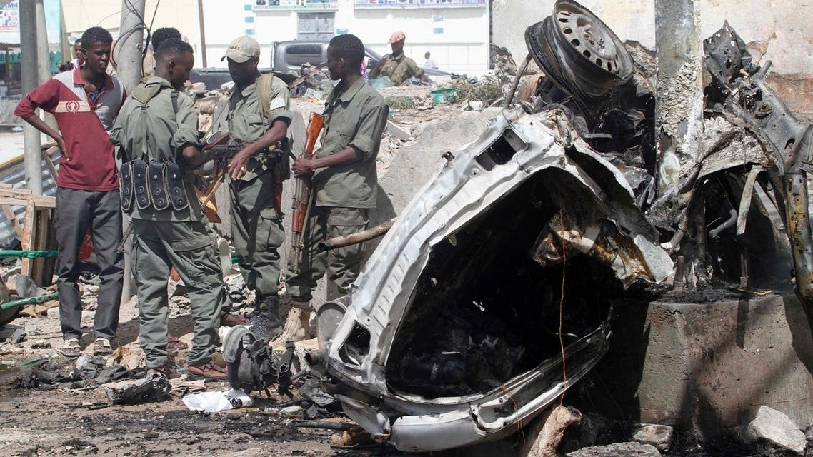 """Officers stand by the remains of a wrecked car at the scene of car bomb explosion along the """"Kilometre 4"""" road junction, south of the capital Mogadishu, May 5, 2013. (Reuters)"""