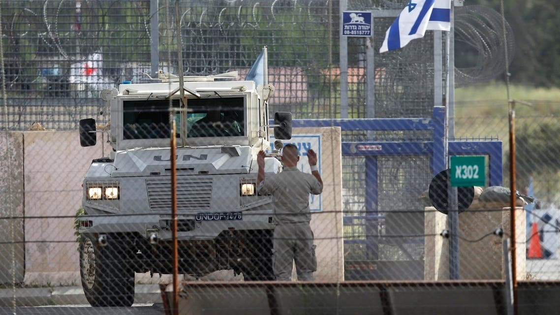 A United Nations peacekeeper directs an armoured vehicle after it crossed from Syria to the Israeli-occupied Golan Heights at the Kuneitra border crossing May 8, 2013.(reuters)