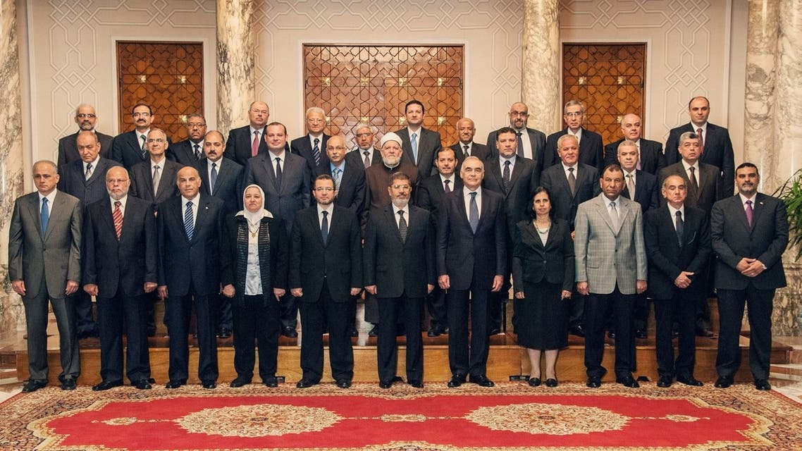 President Mohammed Mursi (centre) with Prime Minister Hisham Qandil and nine new cabinet ministers during a meeting in Cairo. (AFP)