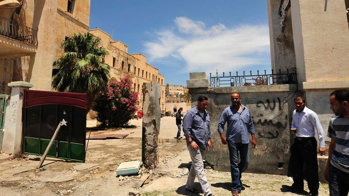Libyans stand next to the scene of a blast after a bomb exploded outside a police station in Benghazi May 10, 2013. (Reuters)