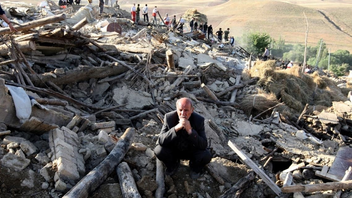 A resident from the village of Baje-Baj, near the town of Varzaqan, sits on top of the rubble of his destroyed home on August 12, 2012. (Atta Kenare/AFP/GettyImages) #