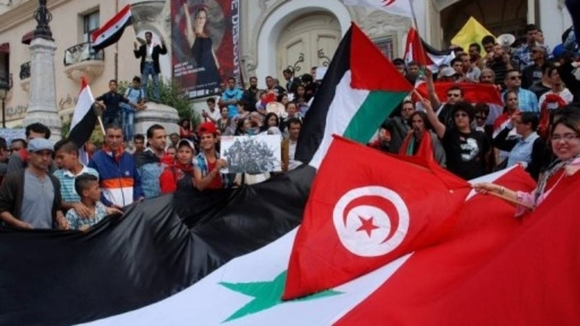 Tunisian protestors hold Syrian flags AFP