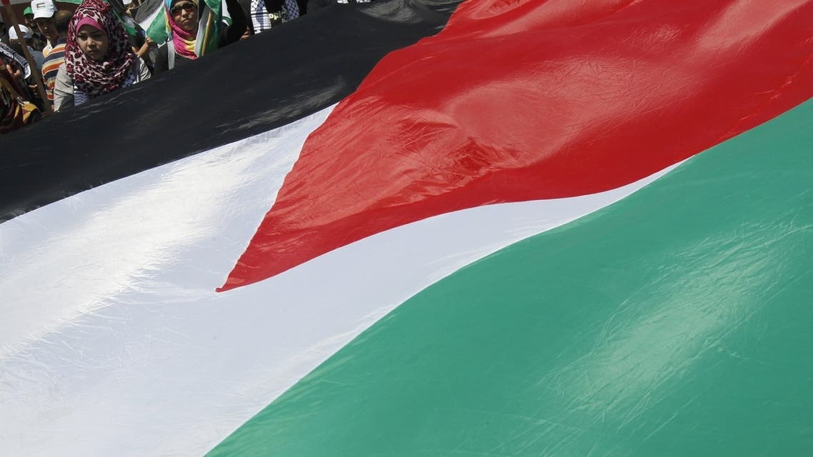 """Palestinians watch a huge Palestinian flag being paraded during the 65th Nakba day or """"Day of Catastrophe"""" rally in Gaza City, on May 15, 2013. (AFP)"""
