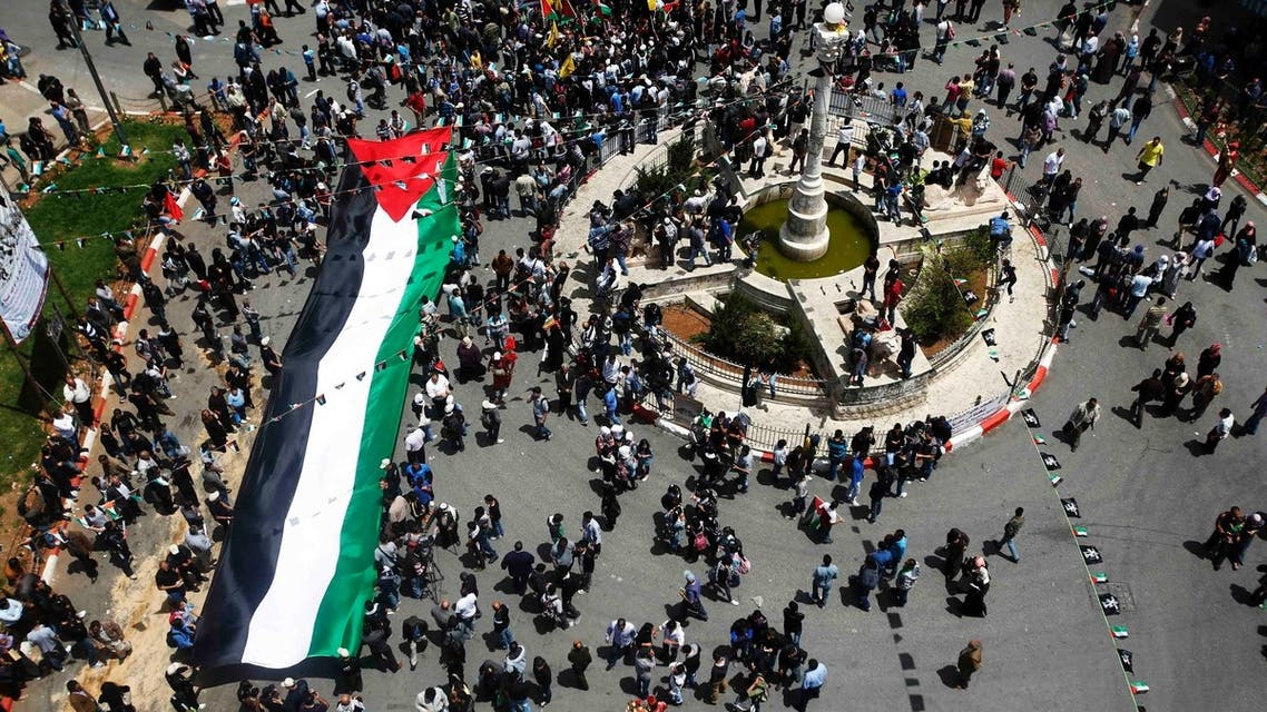 Palestinians carry a giant Palestinian flag through central Ramallah during a rally to mark Nakba Day in the West Bank city of Ramallah May 15, 2013. (Reuters)