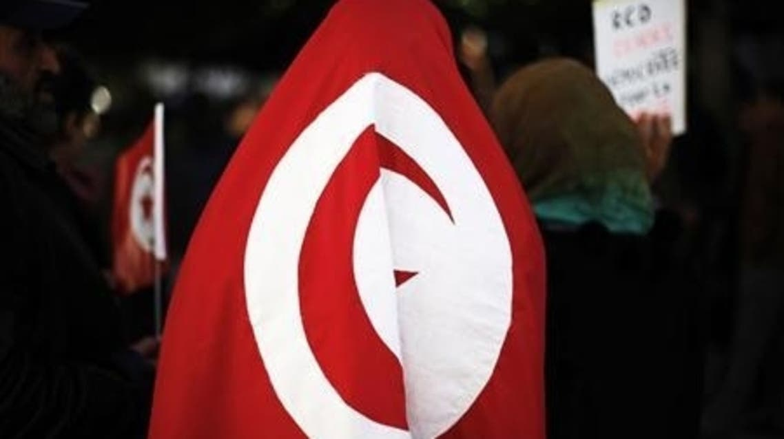 A female protester wears a Tunisian flag in front of the Prime Minister's office during a demonstration in downtown Tunis, January 21, 2011. (Reuters)