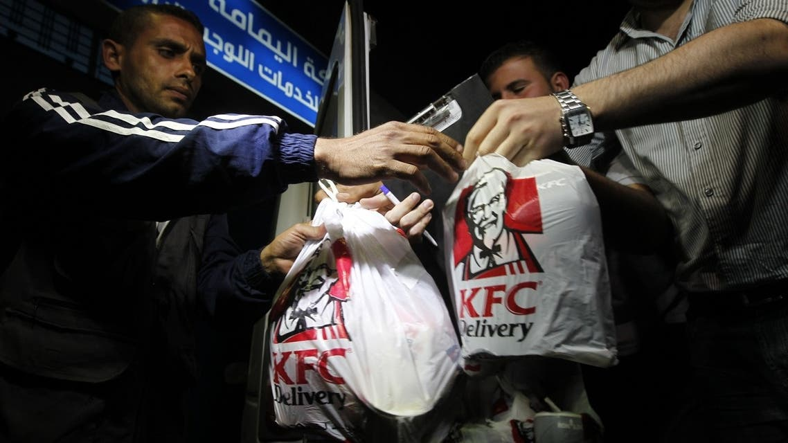 Delivery employees carry bags of food from Kentucky Fried Chicken after it arrived in Gaza City through an underground tunnel linking the Gaza Strip to Egypt, on May 16, 2013. (AFP)