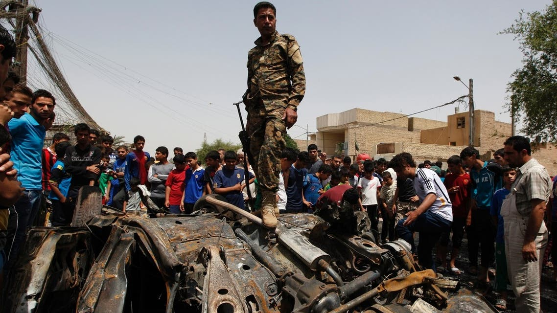 An Iraqi soldier steps over wreckage of a car bomb at the site of a car bomb attack in Baghdad's Sadr City May 16, 2013. (REUTERS)