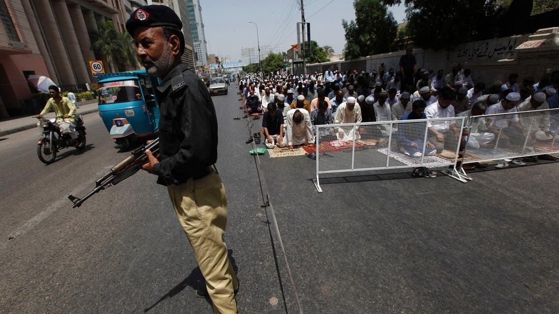 A policeman stands guard where men participate in Friday prayers, near a mosque, along a road in Karachi May 17, 2013. (Reuters)