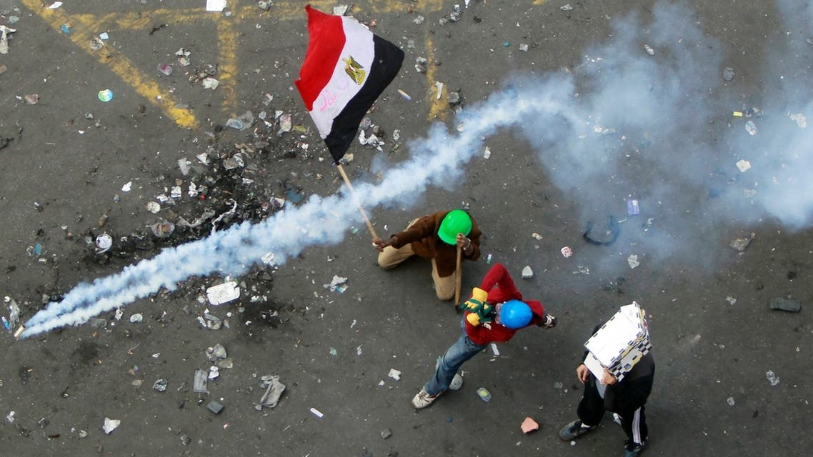 A protester throws a tear gas canister, which was earlier thrown by riot police, as another protester waves the Egyptian flag at Tahrir Square in Cairo November 21, 2011. (Reuters)